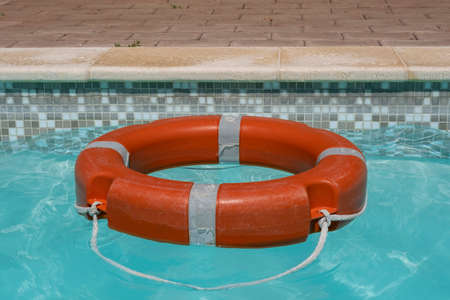 Red life buoy floating in swimming pool.