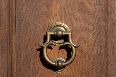 Vintage ornamented image of ancient door knocker on a wooden door. 免版税图像