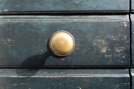 Classic retro brass door knob on green door vintage decoration retro interior style. 免版税图像