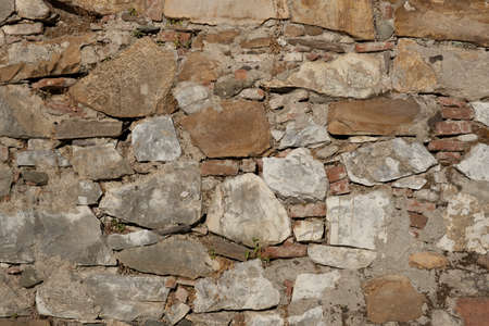 Wall texture of ancient old brick stone. Outdoor exterior  facade with destroyed uneven pattern of shabby rock. Solid wall sandstone structure background. Grunge surface useful for 3d texturing