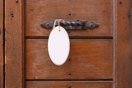 Antique door handle on a wooden door with a white sign hanging on a door.