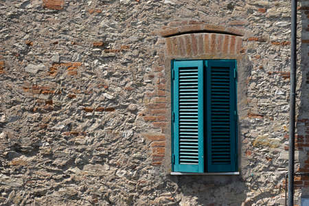 old wooden window on brown brick wall background, stone wall with little window.