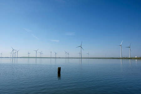 Modern windmills in the water near the shore along a green grassy dike in the netherlands