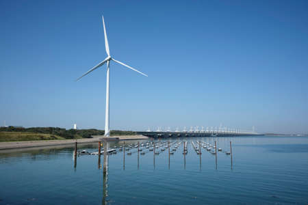 the zeelandbrug deltaworks in holland at the Oosterschelde river to protect holland form high sea level, this is near the dutch museum neeltje jans with windmills as background 免版税图像