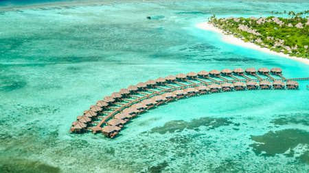aerial view of irufushi island with water bungalows and coast, maldives