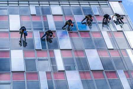 six young men are cleaning windows on high glassy building photo