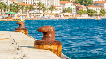 mediterrean: two abandoned iron rusty piers in a mediterrean harbor with a village as background