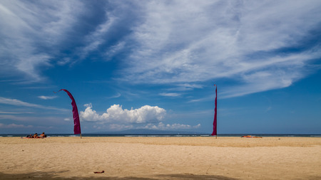 sanur: beach in bali, sanur, sunbathing people and two red flags, hot and wet spring day