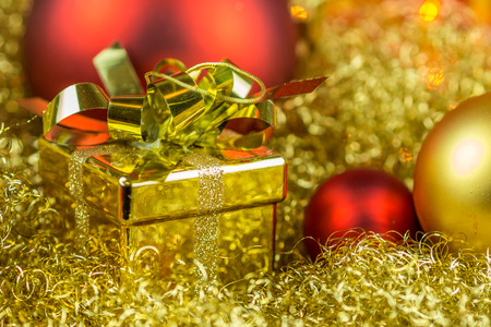 gloden: Christmas gift and balls on gloden background