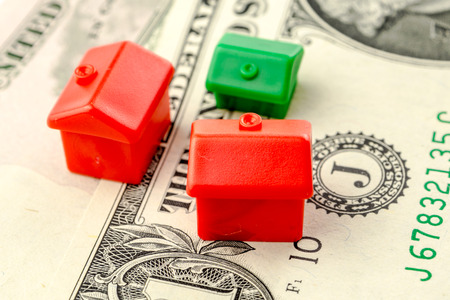money issues: three little houses made of plastic are laying on one dollar banknote, business concept Stock Photo
