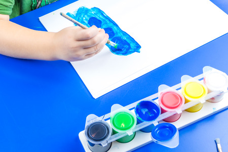 tempera: child is painting a picture with tempera paints on blue table