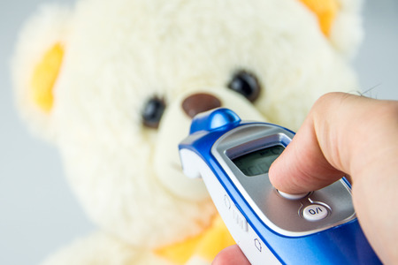 tele: measuring temperature with tele thermometer of baby teddy bear
