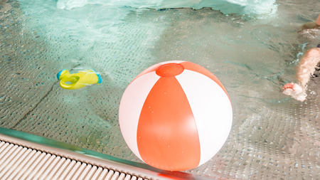 child, slide, watering can and red and white inflatable ball are laying on a surface of an indoor rustless baby pool photo