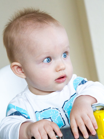baby on chair: baby boy is sitting on a baby chair and playing with a toy Stock Photo