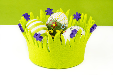 closeup view of easter multicolored eggs in green basket on white and green background photo