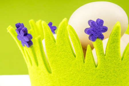 closeup view of eggs in green basket with easter theme on white and green background photo