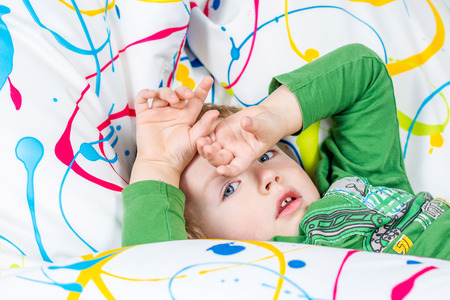 young boy is covering his eyes while lying on multicolored sitting bag photo