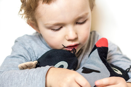moles: young boy is holding two moles made of plush