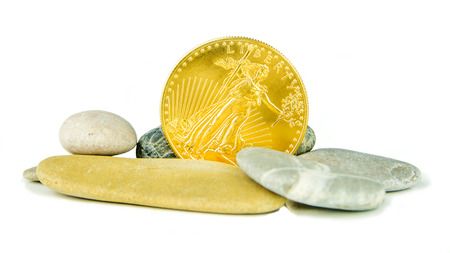 pebblestone: golden american eagle coin with grey pebblestones on white background Stock Photo