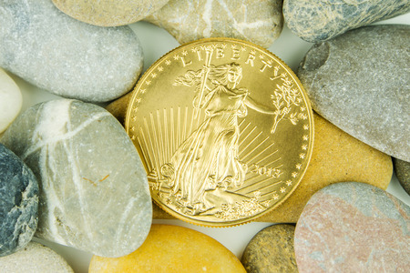 american currency: golden ounce of american eagle coin hidden under pebble stones