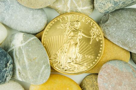 aguila dorada: oz de oro de la moneda de �guila americana escondido bajo las piedras del guijarro