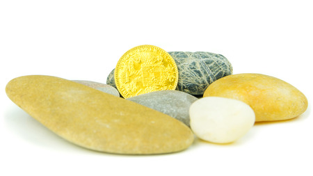 pebblestone: golden ducat coin with grey pebblestones on white background