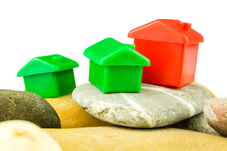 pebblestone: Three little green and red houses made of plastic are laying on bunch of grey pebblestones