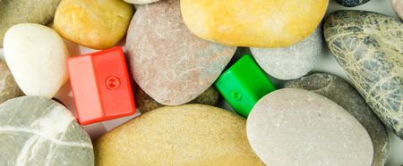 red pebble: two red and green miniatures of plastic houses laying under differrent pebble stones Stock Photo