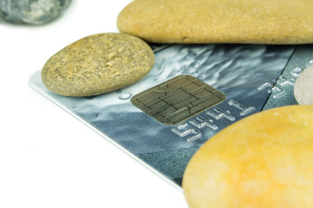 frail: grey debit card is laying under various pebble stones
