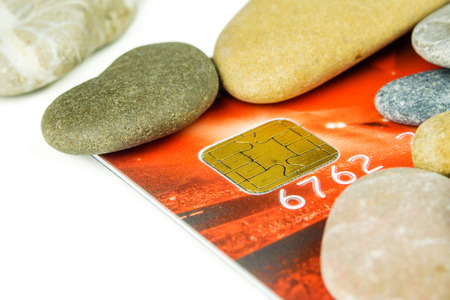red pebble: red debit card is laying under various pebble stones