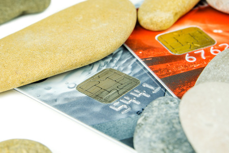 red pebble: grey and red debit cards are laying under various pebble stones