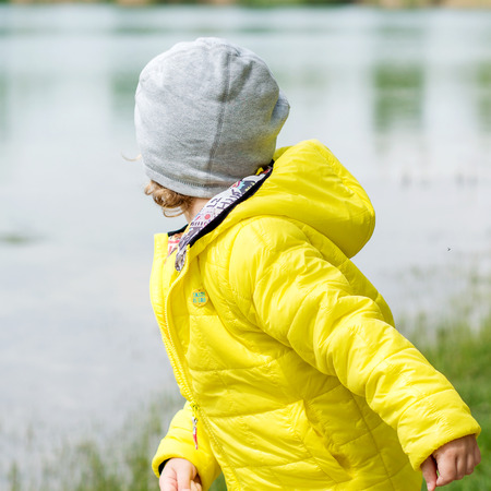 yellow jacket: young boy in yellow jacket is playing on lake shore