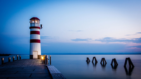 red striped lighthouse in one summer evening somewhere in Europe photo
