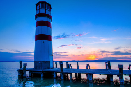 somewhere: red striped lighthouse in one summer evening somewhere in Europe