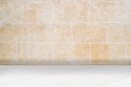 diamond stones: wall made of old uncared orange stones and floor made of little modern beige ceramic diamond mosaic