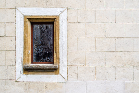 crooked: uncared and crooked wall with old window on one european castle with a lot of scratches and irregularities