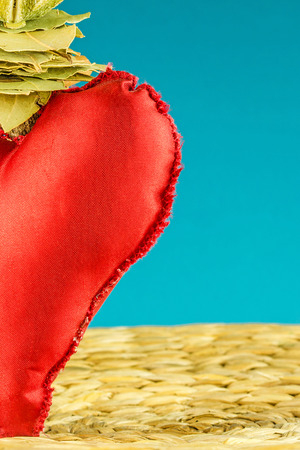 turquise: half of red heart decoration on background made of dry banana leaf with circle texture and turquise color