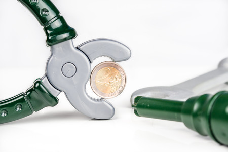 euro screw: combined pliers are holding two euro coin with screw driver and key on white background