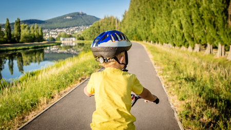 decide: young boy is sitting on a bike and has to decide whether start or not Stock Photo