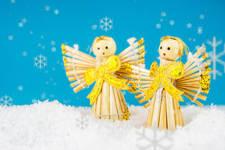 fragile peace: two straw angels laying on snow with turquoise background Stock Photo