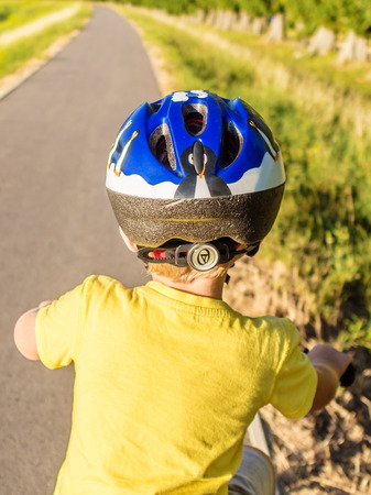 whether: young boy is sitting on a bike and has to decide whether start or not Stock Photo