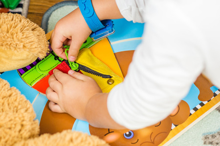 up do: child is learning to do up zip with a special toy Stock Photo