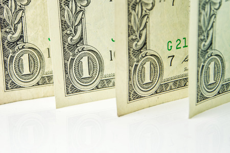 four in one: four one dollar banknotes standing one after another on white background