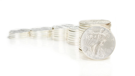 ounce: columns made of silver coins as growing chart pattern with one standing ounce of silver eagle Stock Photo