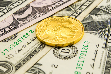 monetary devaluation: golden buffalo coin laying on one and five dollar banknotes