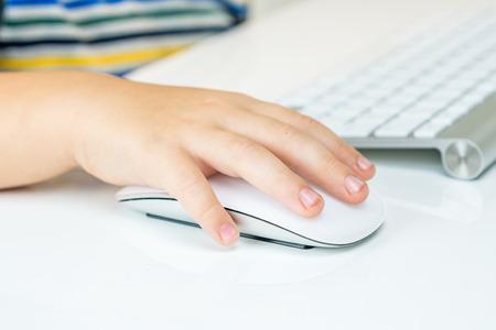 myszy: Młody chłopak siedzi na krześle i pracy poważnie z myszy komputerowej, zbliżenie