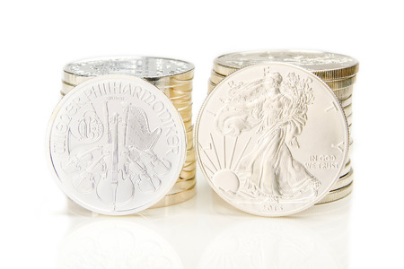 ounce: two columns of silver coins with one ounce of phillharmoniker and american eagle in front of each column