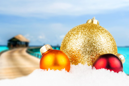 ponton: christmas theme with maldives blurred background, wooden bungalows in the background and three multicolored christmas balls in the front Stock Photo