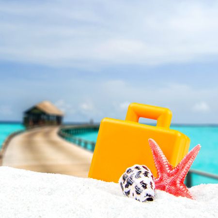 tropical theme with with maldives blurred background, wooden bungalows in the background and one orange suitcase and star shell in the front Stock Photo