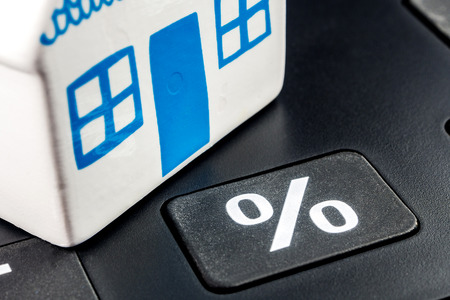 mortgage rates: big black calculator with big percentage button and one ceramic miniature of a house